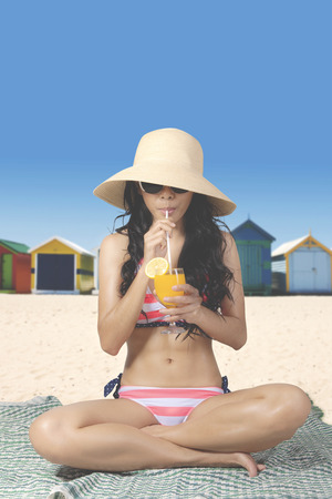 brighton: Summer Concept. Young woman drinks a glass of fresh orange juice while sitting on the beach and wearing a striped bikini with straw hat