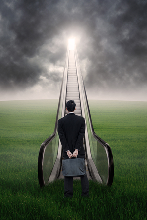 Businessman looking up at escalator under cloudscape photo