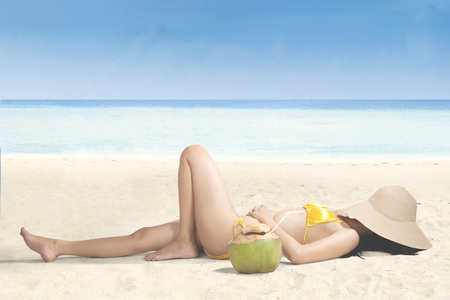 Young woman relaxing on the beach while covering her face with straw hat photo