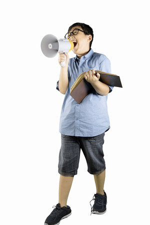 Full length of boy student speaking on megaphone while holding a book, isolated on white background