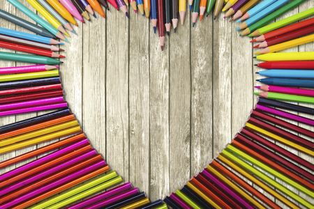 bunch of hearts: Close up of multicolor pencils and heart symbol on the wooden background Stock Photo