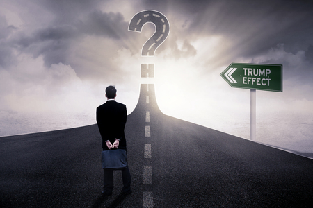 Image of a male entrepreneur standing on the road with Trump Effect word on the signpost and a big question mark photo