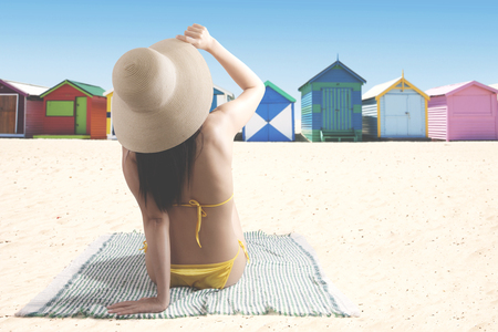 Back view of Asian woman wearing swimsuit and hat while enjoying summertime near the cottage photo