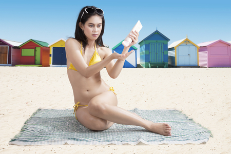 Asian woman wearing swimsuit while applying sunscreen and sitting on the mat near the cottage photo