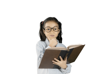 Picture of a little clever girl studying with a book while daydreaming in the studio, isolated on white background Stock Photo