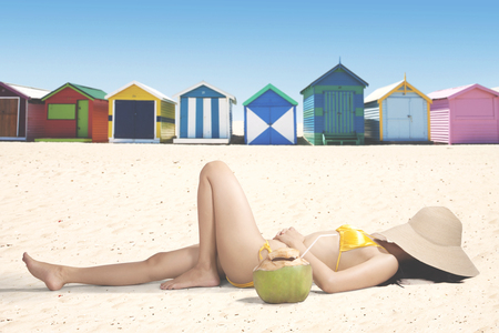 Young woman lying on the white sand while covering her face with straw hat near the cottage photo