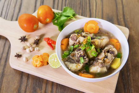 Top view of a bowl of tasty oxtail soup on wooden table, shot in the restaurant