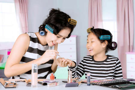 coloration: Image of young mother doing makeup while painting nails her daughter and sitting in the bedroom