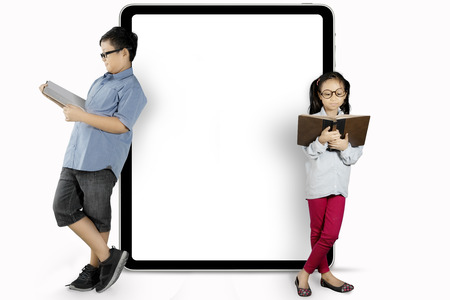 Two children leaning on a blank chalkboard while reading a book in the studio, isolated on white background