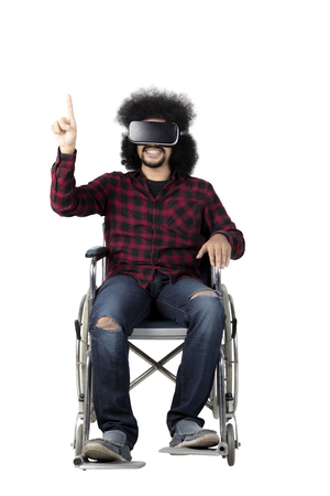 african student: Afro man student wearing Virtual Reality glasses while sitting on a wheelchair, isolated on white background