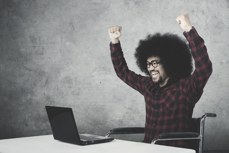 Handicapped Afro man celebrating his success while sitting on wheelchair and working with laptop Stock Photo