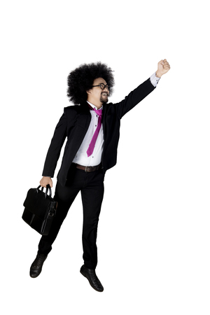 Young Afro businessperson with curly hair, jumping in the studio while holding briefcase and wearing formal suit. Isolated on white background