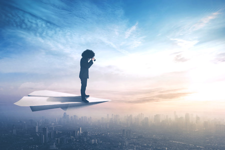 Portrait of a young businessman standing on paper plane while flying above city and looking through binoculars Stock Photo