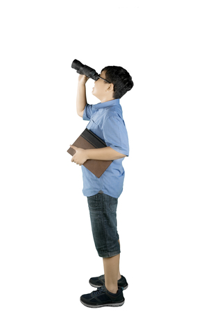 Portrait of schoolboy looking at something with a binocular while holding a book and standing in the studio Foto de archivo