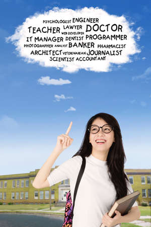 Image of a beautiful college student imagines her dream while pointing a cloud in the sky Stock Photo