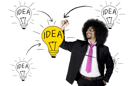 Young Afro businessman with curly hair and wearing formal suit, drawing bright light bulb with idea text
