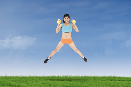 Healthy young woman leaps on the meadow while holding two dumbbells and wearing sportswear photo
