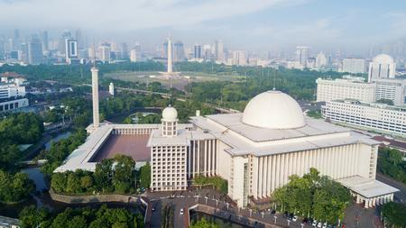 자카르타, 인도네시아에서 푸른 하늘 아래 Istiqlal 모스크와 고층 빌딩 도시의 파노라마