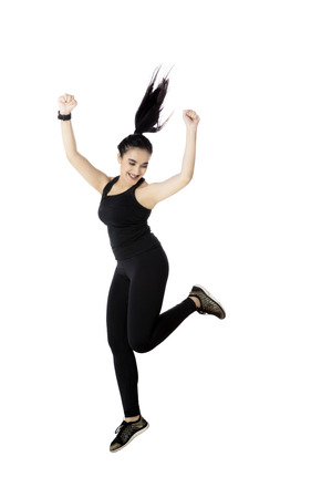 Portrait of a beautiful woman wearing sportswear while jumping in the studio, isolated on white background