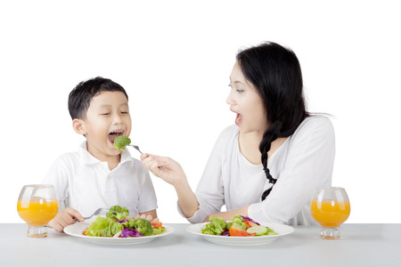 Image of pretty young mother feeding her cute son with healthy food while sitting in the studio, isolated on white background
