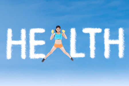 Young woman holding dumbbells and jumping on the sky with cloud shaped Health word photo