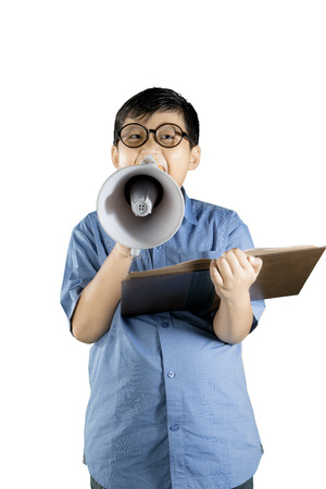Portrait of a boy student reading a book while shouting with a megaphone, isolated on white background