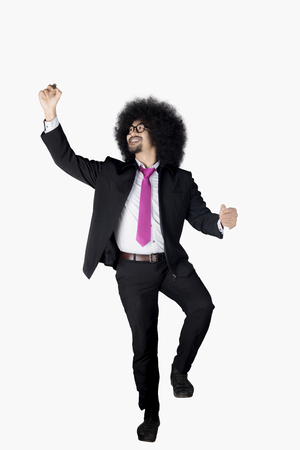 Full length of Afro businessman with curly hair, using a marker to write on whiteboard. Isolated on white background