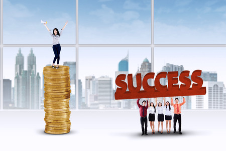 Image of business team lifting a word of success with the leader standing on the golden coins, shot in the office photo