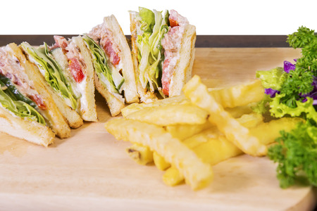 cutting: Closeup of delicious sandwich and french fries in a cutting board on wooden table at the restaurant Stock Photo