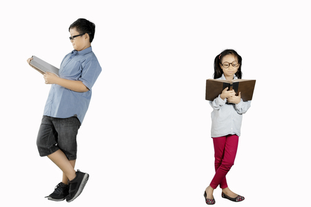 Image of two children reading a book while learning together with a book in the studio, isolated on white background Stock Photo