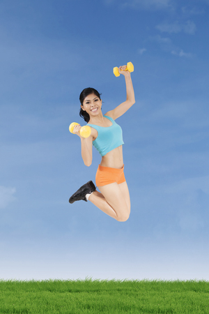 Sporty woman jumping on the meadow while wearing sportswear and holding two dumbbells photo