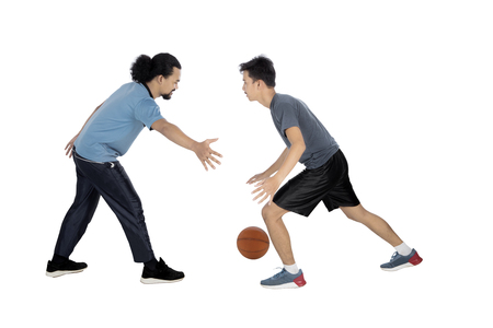 Full length of two young multiracial men playing basketball in the studio, isolated on white background
