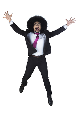 Successful Afro businessman jumping with arms raised isolated on white background