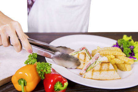 junk: Closeup of woman hand using a tong to serve tasty sandwich with french fries and salad Stock Photo