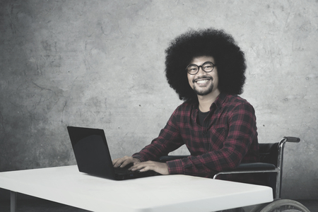 Disabled businessman sitting on the wheelchair and smiling at the camera while working with laptop Stock Photo