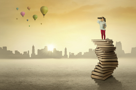diligente: Estudiante femenino de la escuela primaria que se coloca en una pila de libros mientras que mira el cielo a través de los prismáticos