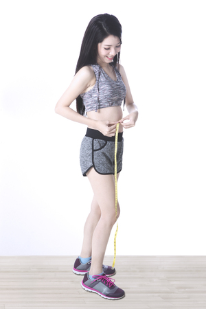 waistline: Sporty young woman with slim body, measuring her waistline with a tape measure while wearing sportswear