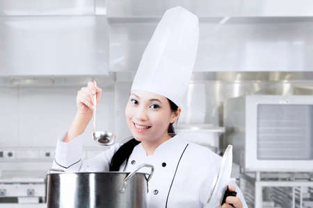 Beautiful female chef cooking with a pot in the kitchen and wearing uniform photo