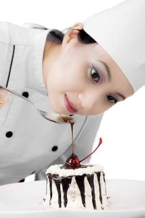 Closeup of pretty female chef garnishing delicious cake with chocolate, isolated on white background photo
