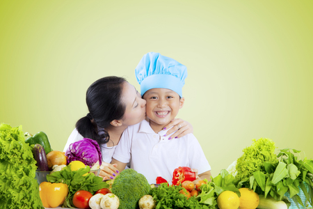 Young woman kissing her son while preparing fresh vegetables on the table, shot with green screen background photo