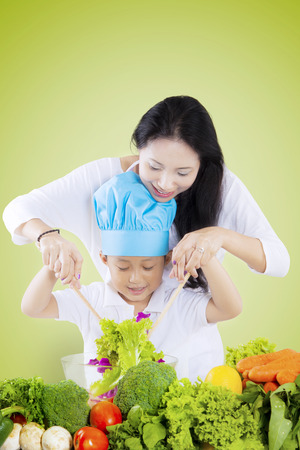 Young Asian mother helping her son make a bowl of vegetables salad, shot with green screen background photo