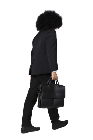 carrying: Portrait of businessman with frizzy hair walking in the studio while carrying briefcase