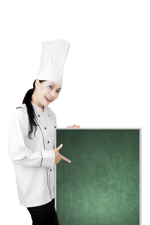 Portrait of a beautiful female chef wearing uniform while pointing a blank chalkboard, isolated on white background photo