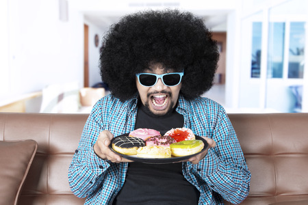 Afro man with curly hair, holding a plate of tasty donuts while wearing sunglasses and sitting on the sofa at home