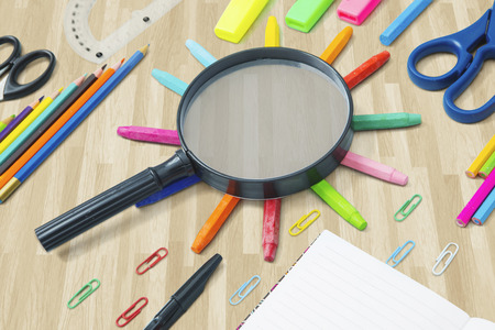 Image of black magnifier above colored crayons with school supplies on the floor
