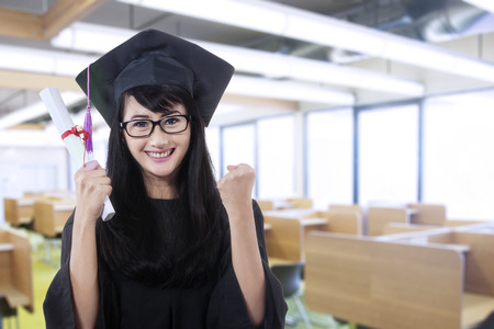 Woman in graduation gown expressing success in the library photo