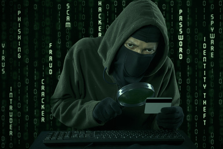 Internet Theft - a man wearing a balaclava looking at credit card code using magnifying glass Stock Photo
