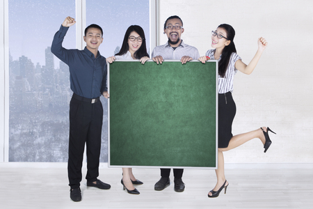 Group of cheerful business team standing in the office while holding a blank blackboard for advertisement Stock Photo