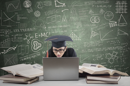 Young female graduate studying with laptop and books on class photo
