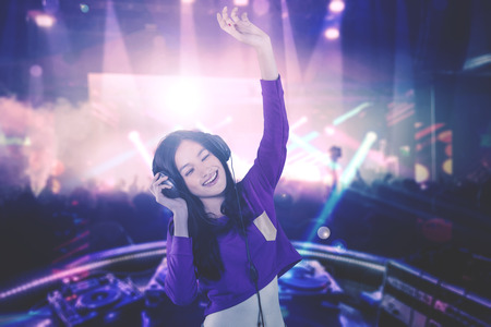 Image of a young DJ looks happy while playing her song for people in the nightclub